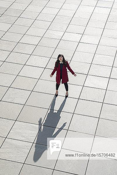 Blick von oben auf eine gehende moderne Geschäftsfrau  die mit offenen Armen auf dem Betonboden steht