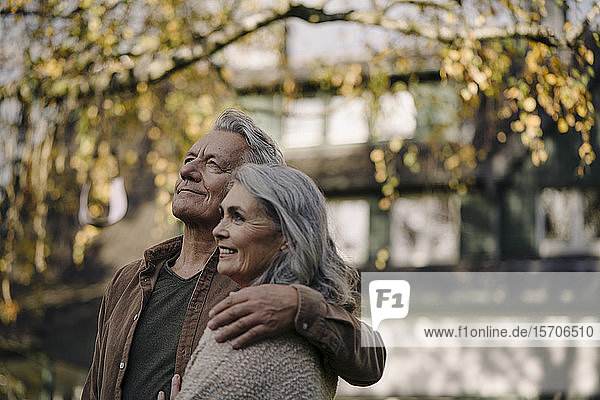 Affectionate senior couple in garden of their home in autumn