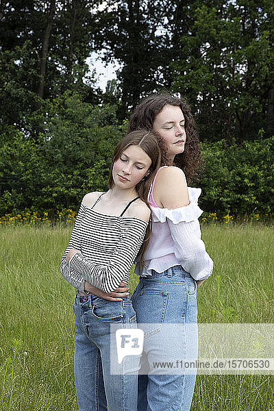 Portrait of two best friends standing back to back on a meadow