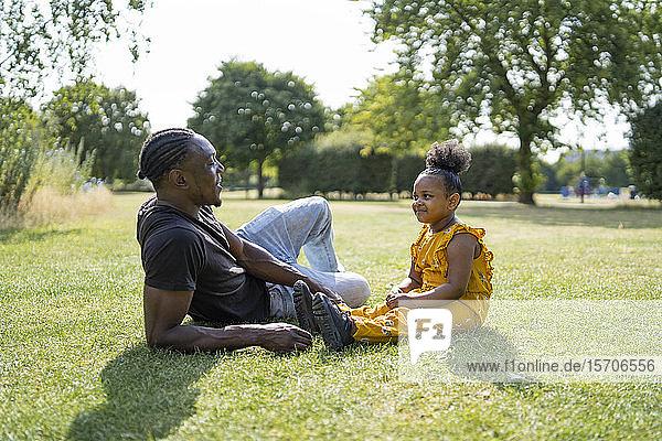 Vater und Tochter entspannen sich auf einer Wiese in einem Park