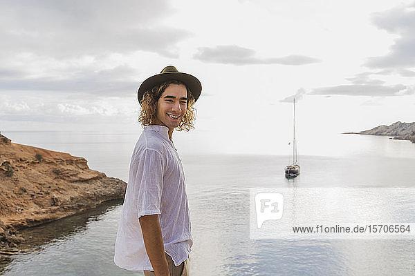 Porträt eines entspannten jungen Mannes vor dem Meer  Ibiza  Balearen  Spanien