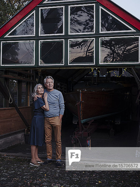 Senior couple standing in front of boathouse