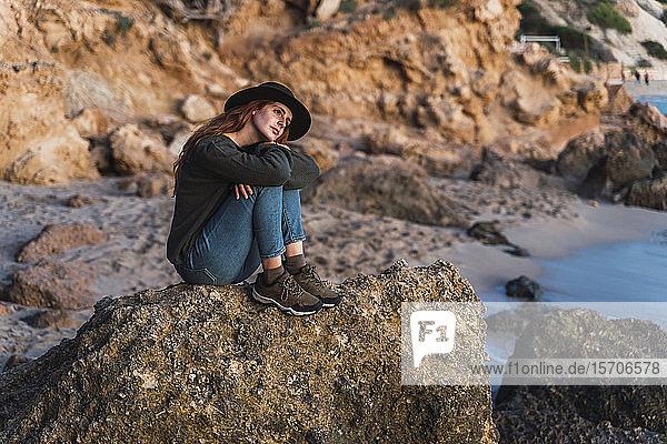 Junge Frau sitzt am Strand und genießt den Sonnenuntergang  Ibiza