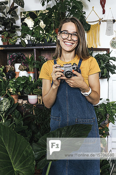 Portrait of a happy young woman with a camera in a small gardening shop