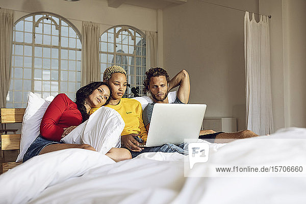 Friends relaxing in bed at home watching a movie on laptop