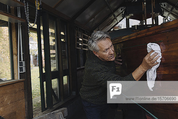 Senior man cleaning wooden boat in a boathouse