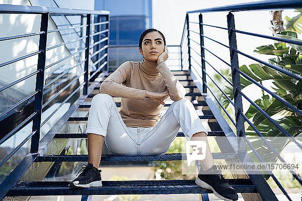 Junge Frau sitzt auf einer Außentreppe