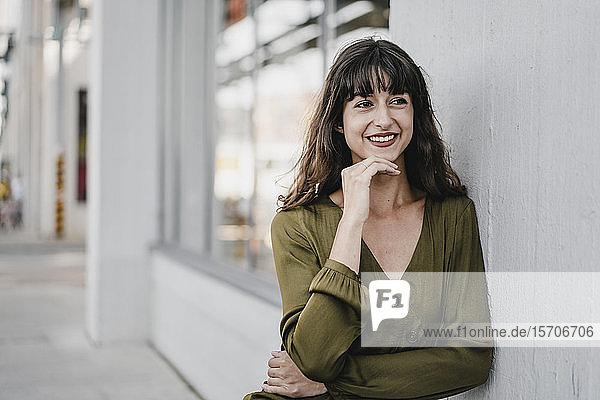 Portrait of smiling brunette woman leaning on a wall  looking sideways