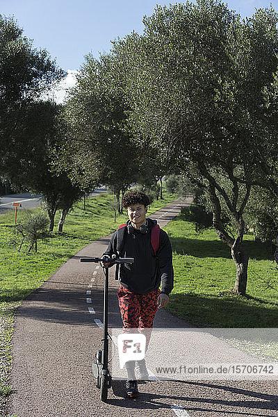 Porträt eines lächelnden jungen Mannes mit E-Scooter auf dem Fahrradweg