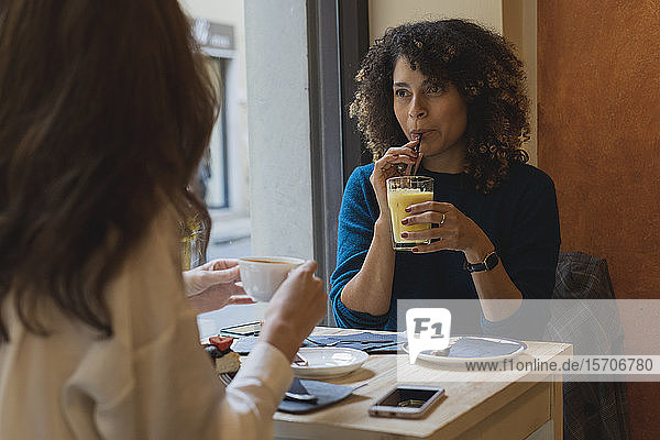 Two women meeting and talking in a cafe