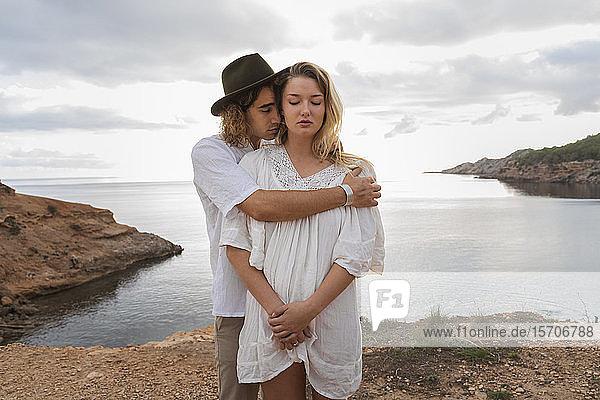 Porträt eines jungen verliebten Paares  das mit geschlossenen Augen vor dem Meer steht  Ibiza  Balearen  Spanien