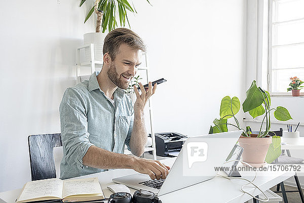Smiling man using smartphone and laptop at desk in office