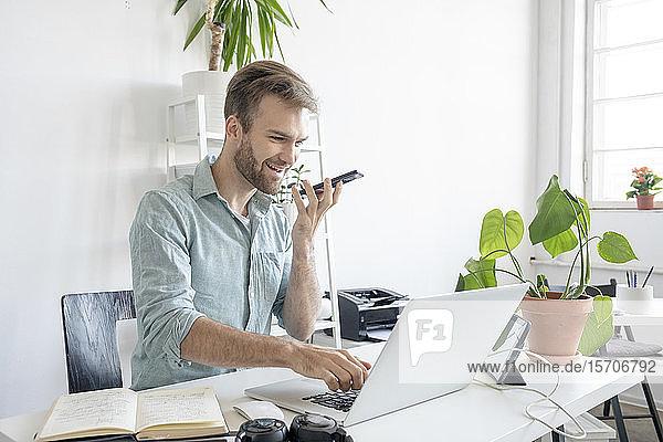 Lächelnder Mann mit Smartphone und Laptop am Schreibtisch im Büro