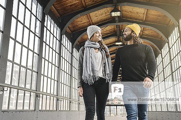 Glückliches junges Paar geht Hand in Hand an einer U-Bahn-Station  Berlin  Deutschland