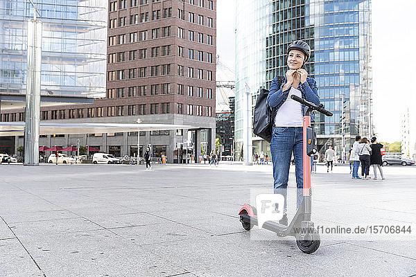 Frau mit E-Scooter in der Stadt  die einen Helm aufsetzt  Berlin  Deutschland