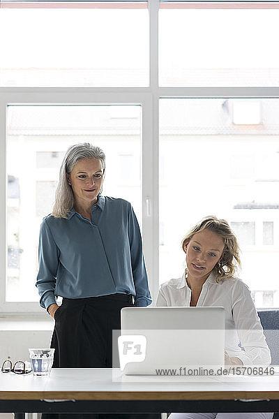 Zwei Geschäftsfrauen benutzen gemeinsam einen Laptop am Schreibtisch im Büro
