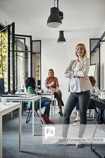 Porträt einer selbstbewussten schwangeren Geschäftsfrau im Amt mit Kollegen im Hintergrund
