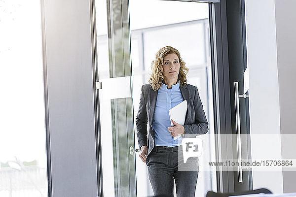 Seriöse Geschäftsfrau mit Tablette im Amt
