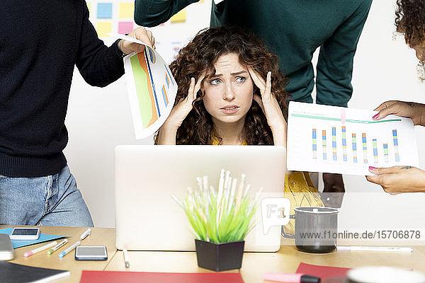 Gestresste Frau sitzt am Schreibtisch im Büro  umgeben von Kollegen