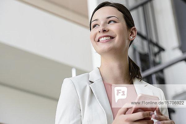 Glückliche junge Geschäftsfrau mit Smartphone im Büro