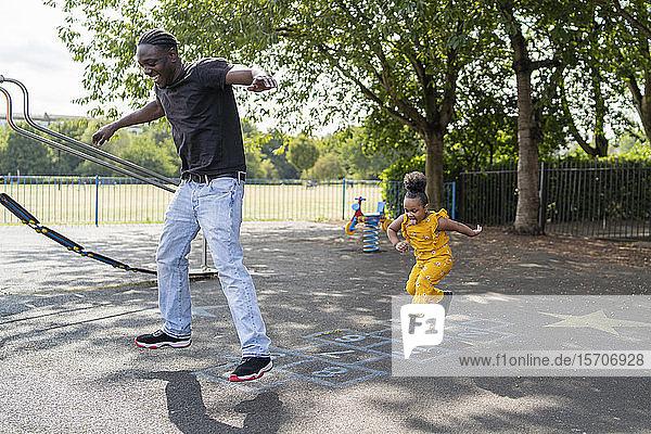 Vater und Tochter beim Hüpfspiel auf einem Spielplatz