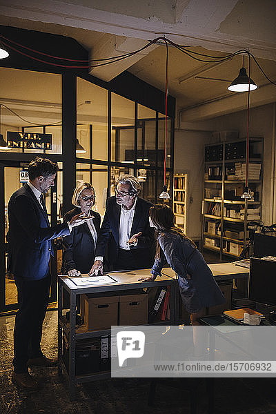 Business people discussing with girl and shining tablet in office