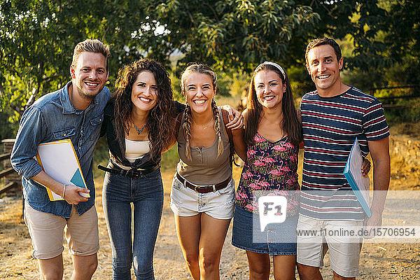 Portait of happy friends on a field trip with folders in rural landscape