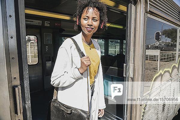 Lächelnde junge Frau steht in Zugtür