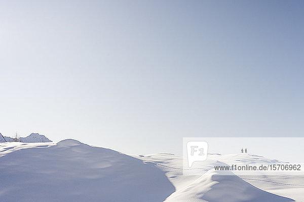 Berglandschaft mit Neuschnee  zwei Wanderer am Aussichtspunkt  Valmalenco  Italien