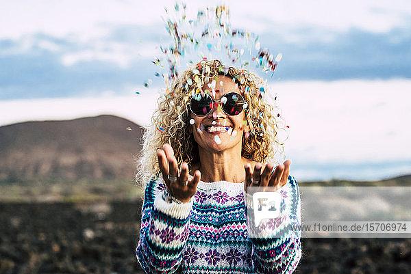 Glückliche blonde Frau wirft Konfetti in die Luft  Teneriffa  Spanien