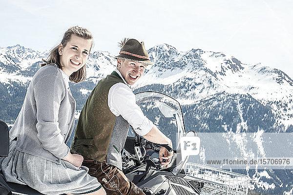 Glückliches Paar in den verschneiten Bergen beim Motorschlittenfahren  Salzburger Land  Österreich