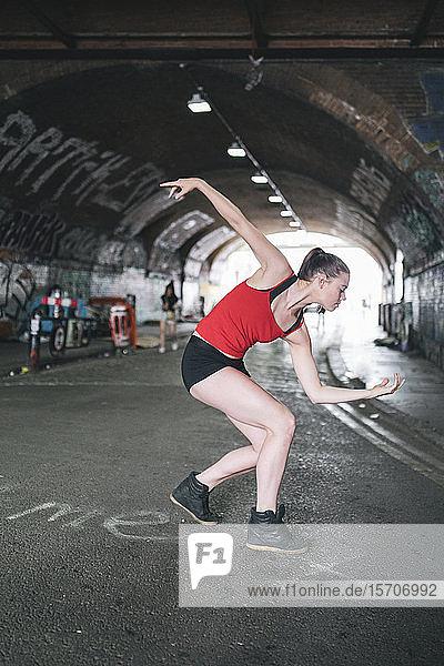 Junge Frau tanzt an einer Unterführung in der Stadt