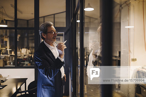 Senior businessman drawing on glass pane in office