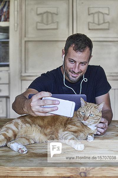Mann sitzt am Tisch und fotografiert seine rothaarige Katze mit einem Smartphone