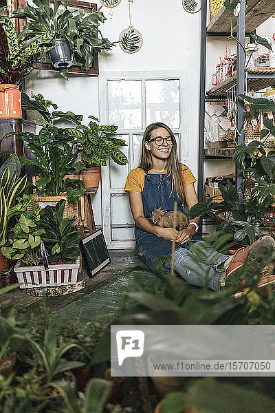 Happy young woman with dinosaur figurine sitting on the floor in a small shop with plants