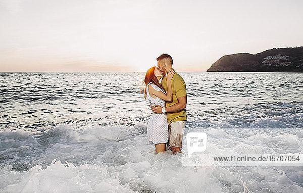 Junges Paar küsst sich bei Sonnenuntergang am Strand