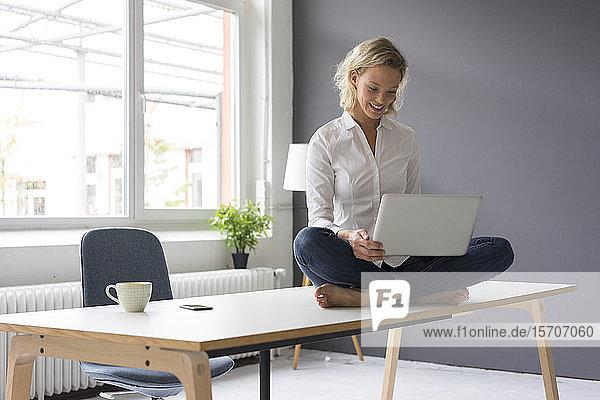 Lächelnde junge Geschäftsfrau sitzt im Büro mit Laptop auf dem Schreibtisch