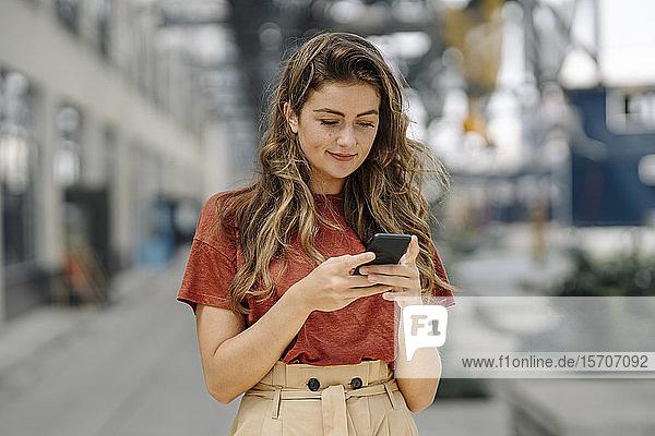 Porträt einer lächelnden jungen brünetten Frau  die ein Smartphone benutzt und nach unten schaut