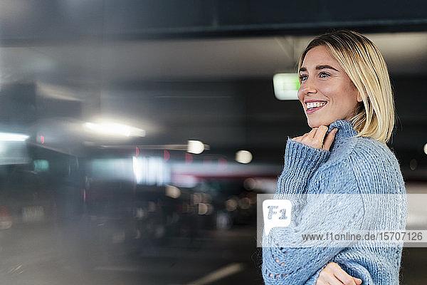 Porträt einer lächelnden jungen Frau in einem Parkhaus