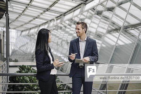 Lächelnder Geschäftsmann und Geschäftsfrau mit sprechenden Tabletten in modernem Bürogebäude