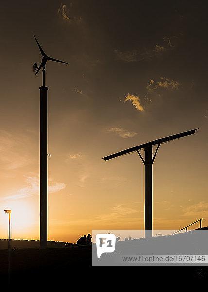 Deutschland  Wuppertal  Bergische Universität Wuppertal  Windturbine  Sonnenkollektor und Studenten bei Sonnenuntergang