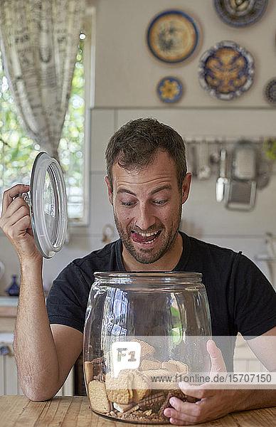 Mann sitzt in der Küche  schaut in die Keksdose  lacht