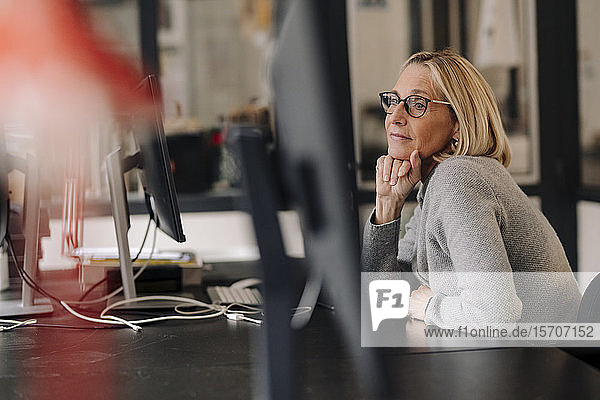 Mature businesswoman sitting at desk in office