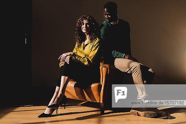 Porträt eines lächelnden Mannes und einer lächelnden Frau im Ledersessel sitzend