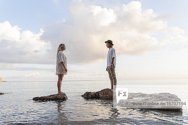 Young couple standing on rocks in front of the sea  Ibiza  Balearic Islands  Spain