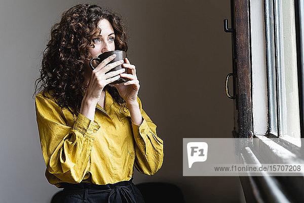 Frau schaut aus dem Fenster und trinkt aus Kaffeetasse