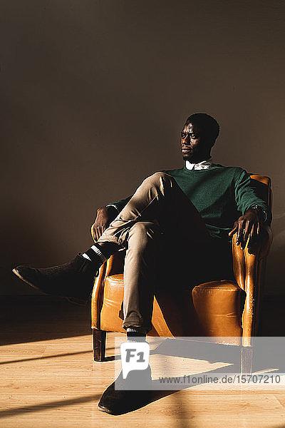 Mann sitzt in Ledersessel und schaut zur Seite