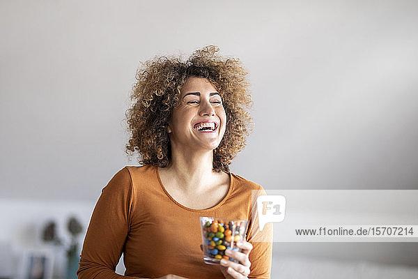 Lächelnde Frau mittleren Alters  die einen Keks isst