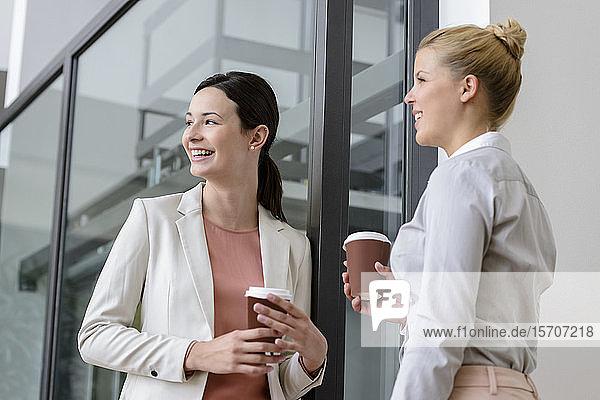 Two smiling businesswomen having coffee break outside office building