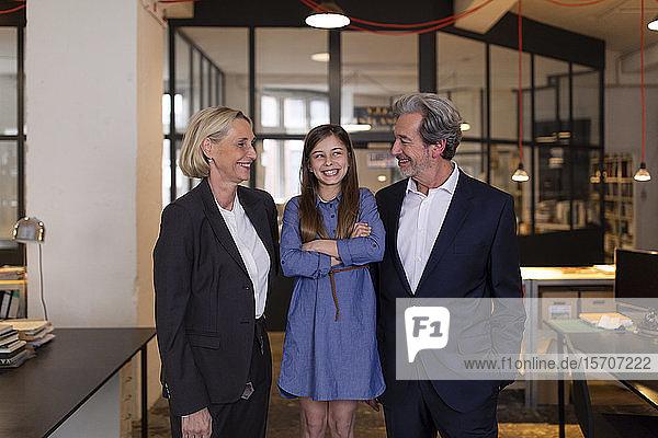 Lächelnder Geschäftsmann und Geschäftsfrau mit Mädchen im Amt
